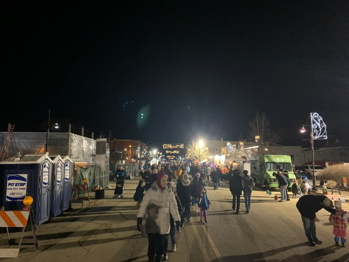 People walk throughout main street during the Christmas Walk.