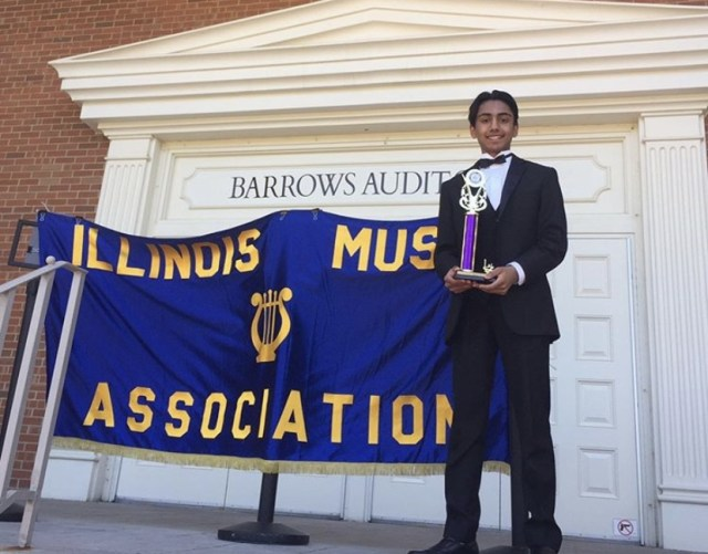 Atharva Iyer poses outside of a music hall with his award from the Illlinois Music Association