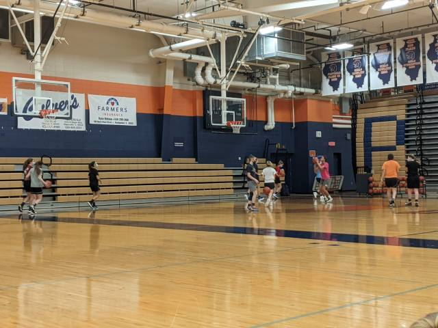 The girls varsity team shooting around in the Oswego High School gym.