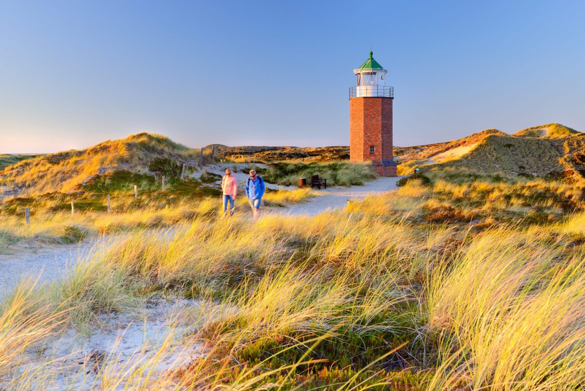 Sylt, Schleswig-Holstein, Germany - Tourists visiting Altes Quermarkenfeuer Rotes Kliff, also called 'Rotes Kill Lighthouse' among Uwe Dunes in Kampen.