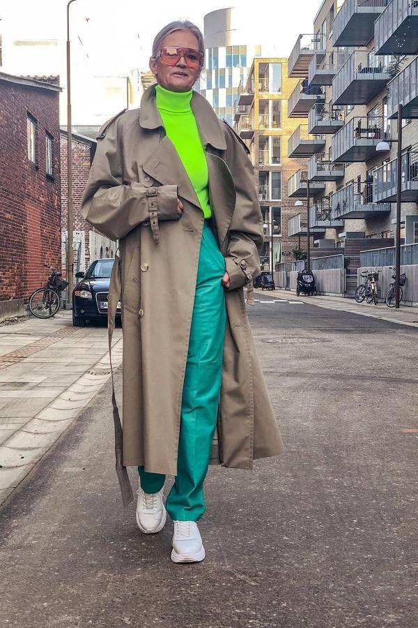 Девушка в бирюзовых брюках, неоновая водолазка, бежевый плащ и белые кроссовки