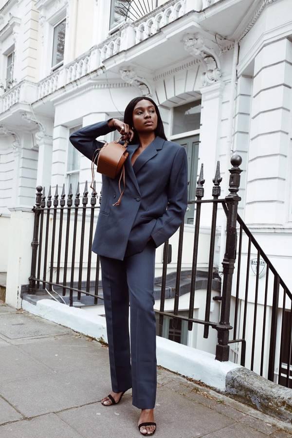 Девушка в черном брючном костюме и босоножках