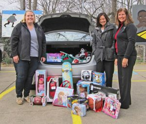 "Sheila Troyer and Kelly Troyer from Everence Financial (right) drop off gifts to Kelly Klein from Lighthouse Ministries (left) for its ""Affordable Christmas"" project.  The annual project makes it possible for parents of at-risk children to buy gifts for their kids at significantly reduced prices."