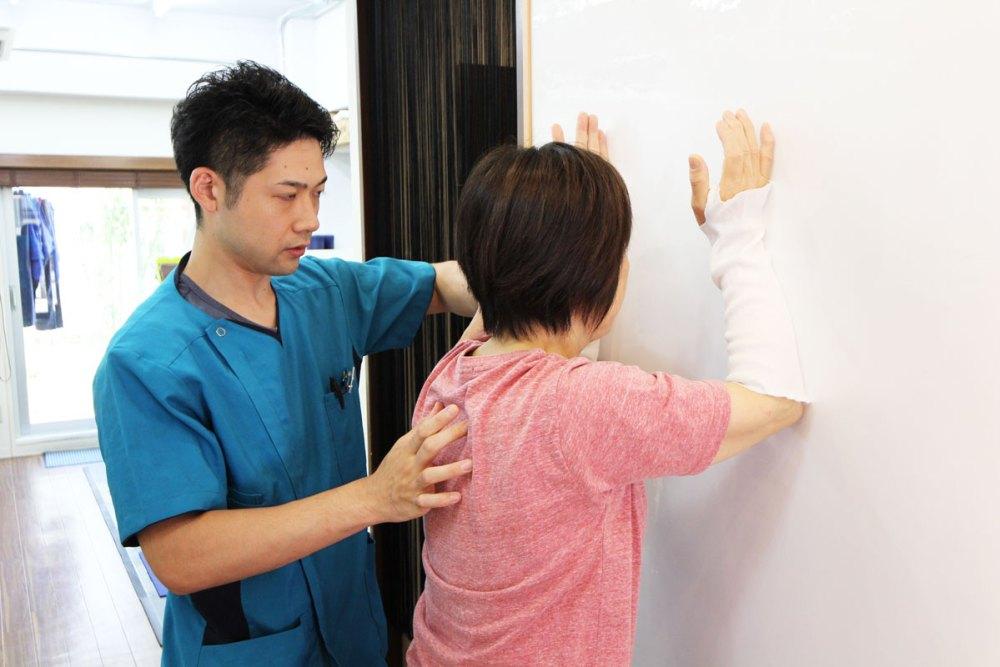 壁で上肢挙上する運動療法