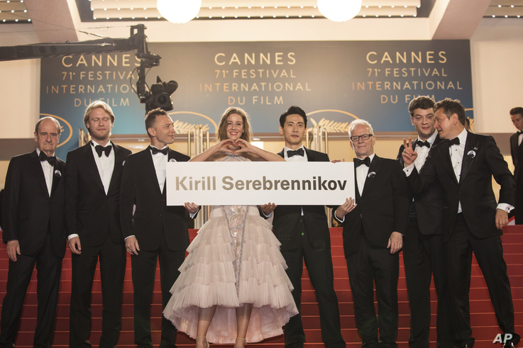 Actress Irina Starshenbaum, centre, holds a sign with the name of the banned director, Kirill Serebrennikov, as she poses with…
