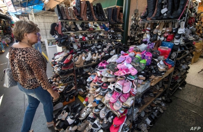 (FILES) In this file photo taken on August 24, 2019 a woman shops for Chinese made shoes at a store in the Chinatown area of Los Angeles, California. Washington is moving ahead on September 1, 2019, with new tariffs on Chinese imports as it steps up…