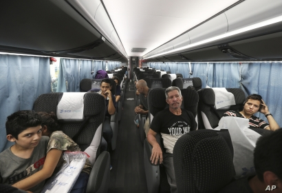 Migrants sit in a bus that will take them and other migrants to Moneterrey, from an immigration center in Nuevo Laredo, Mexico, July 18, 2019.