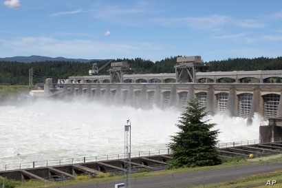 FILE - In this June 27, 2012, file photo, water flows through the Bonneville Dam near Cascade, Ore. Two prominent Pacific…