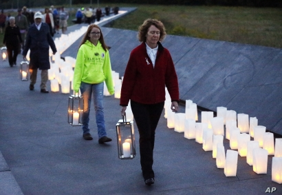 Lanterns are carried during a candlelight memorial to the passengers and crew of United Flight 93, at the Flight 93 National Memorial in Shanksville, Pa, Thursday, Sept. 10, 2015. The new $26 million visitors' complex is expected to draw a larger cro