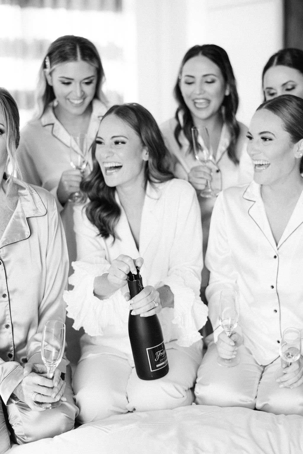 black and white photo of bride and bridesmiads sitting on bed with champagne bottle and wearing matching pajamas.