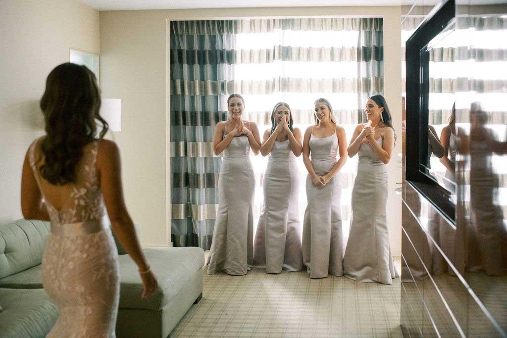 bride reveals her dress to bridesmaids.