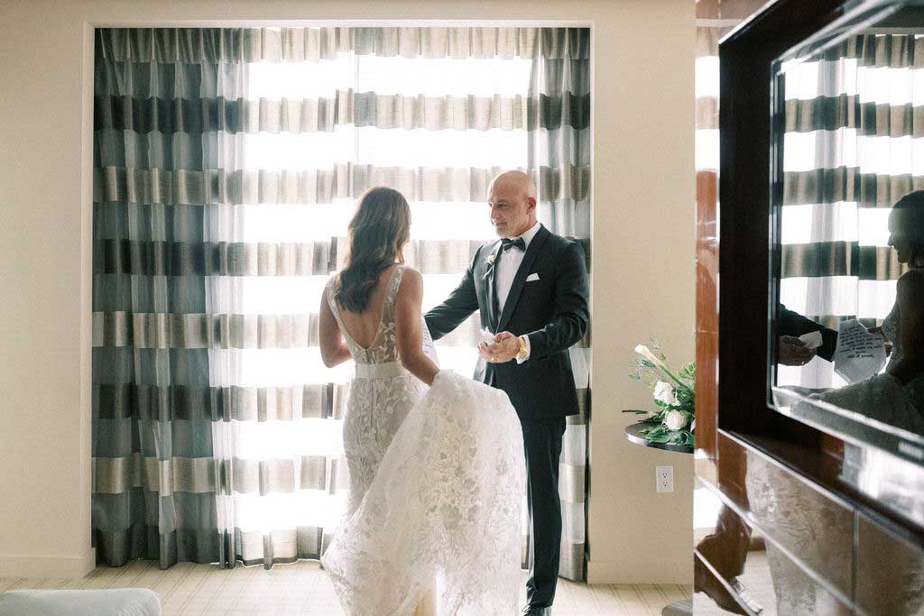 bride reveals her dress to her father in hotel room.