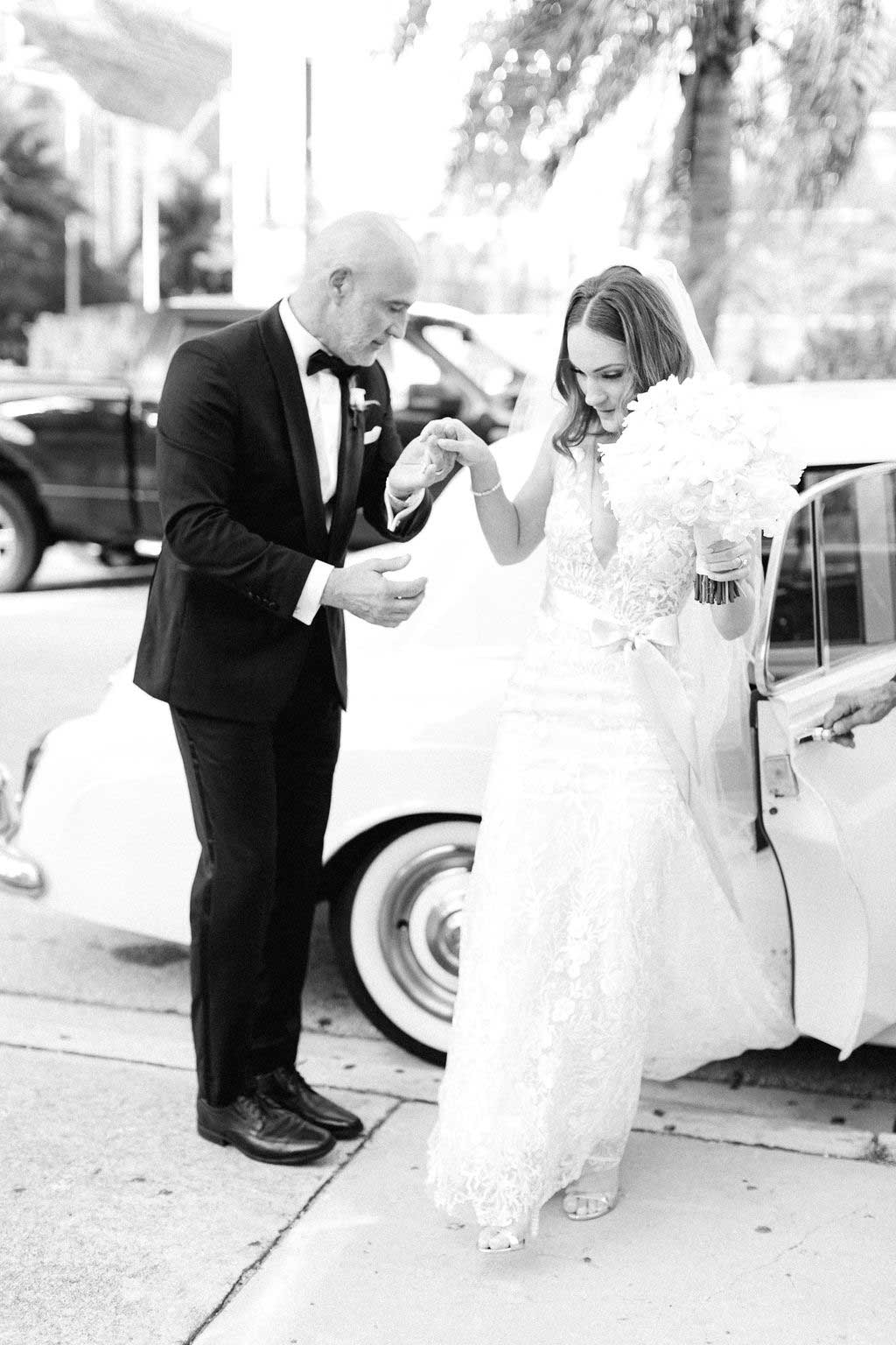 black and white photo of father of the bride helping bride step out of the car.