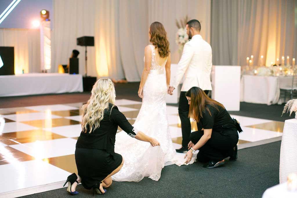 Wedding planners fix brides dress before ballroom reveal.