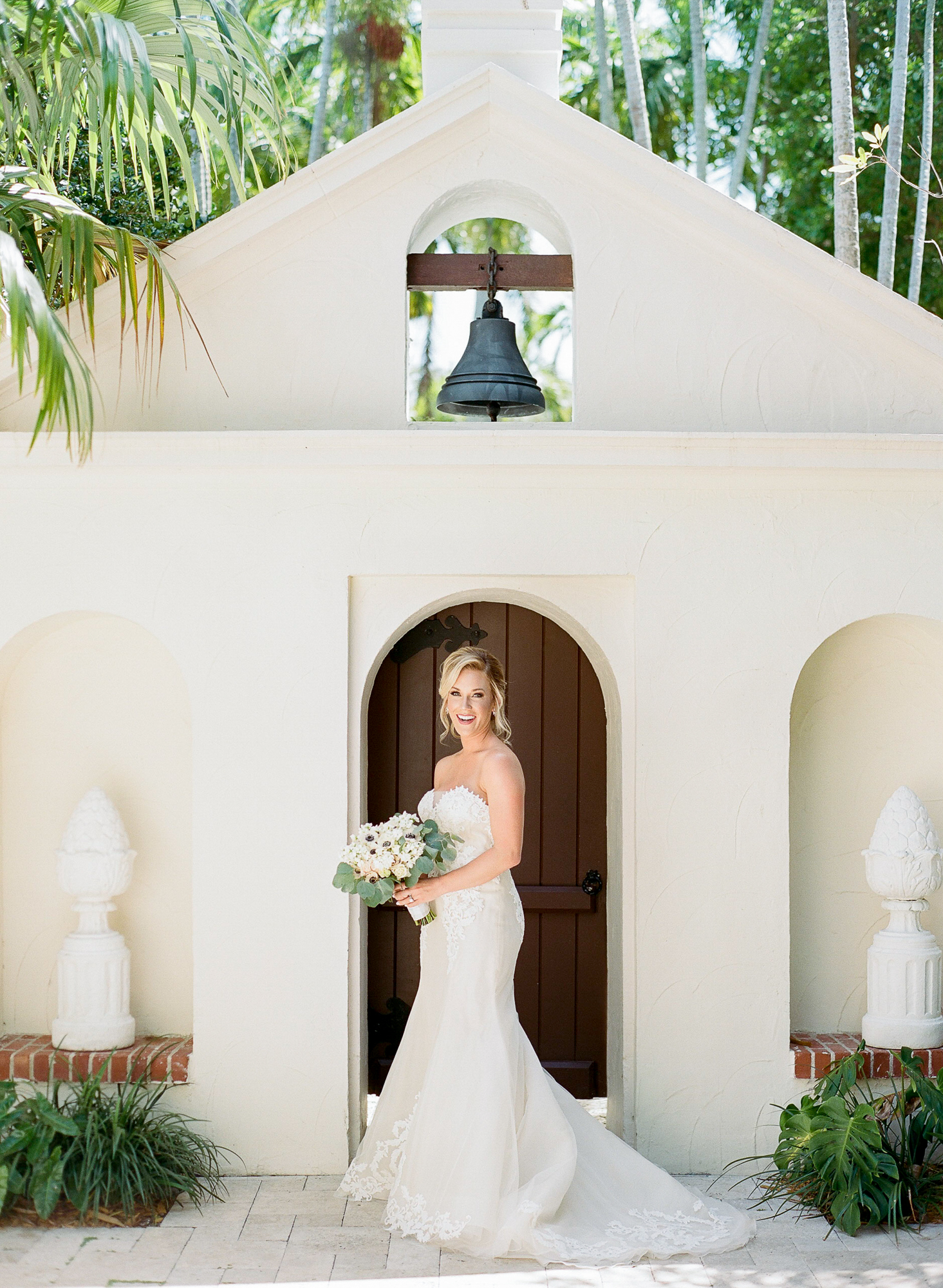 Bride stands in front of door and smiles at the camera with her bouquet wearing a strapless gown.