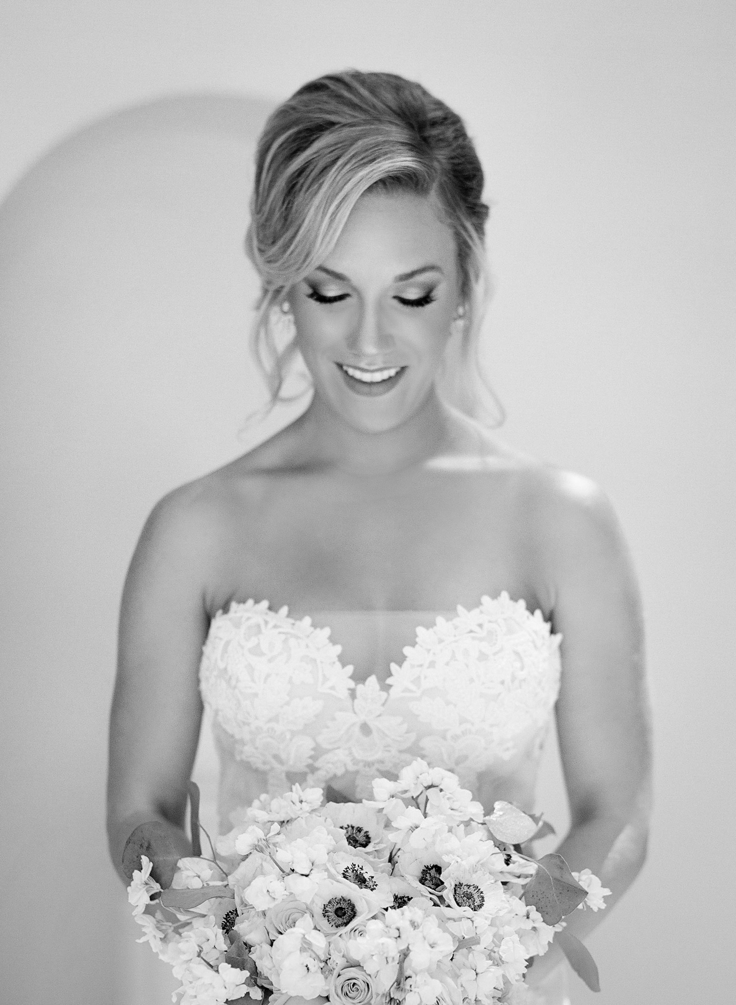 black and white photo of bride smiling down at her bouquet