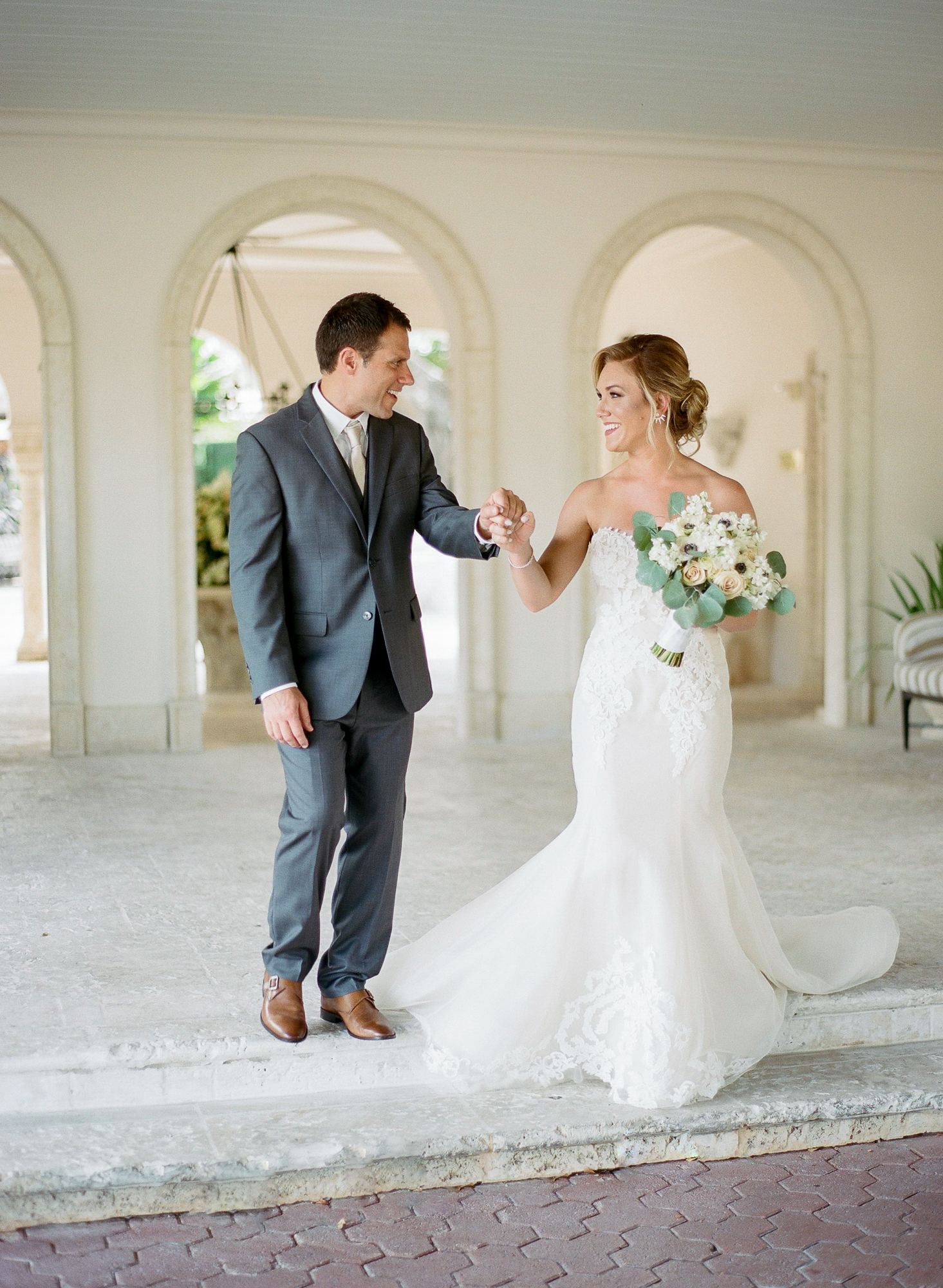 Couple walk towards photographer smiling at each other for their first looks at the Fisher Island Club.