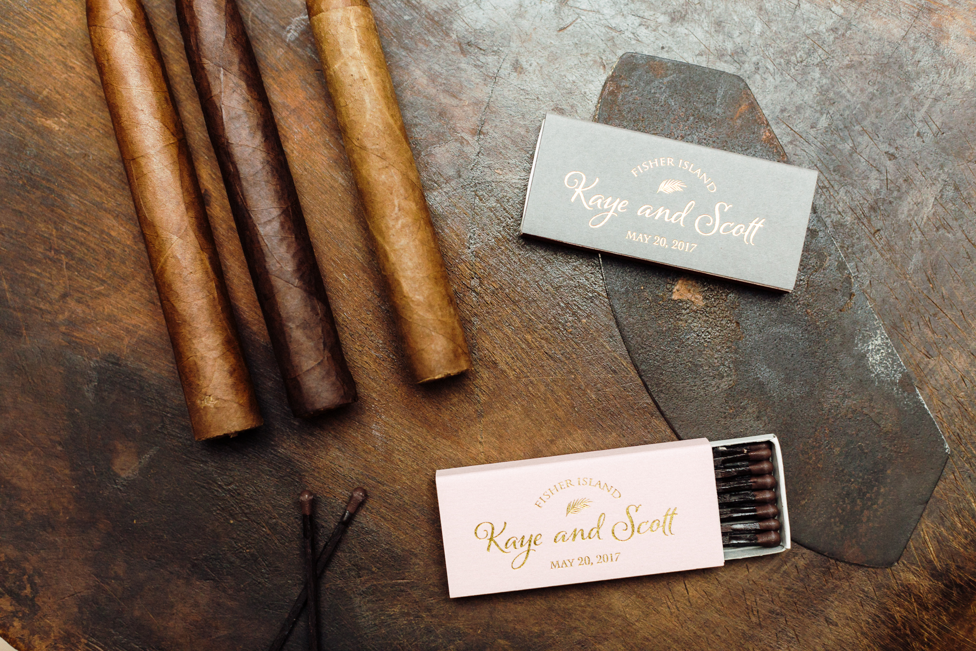Cigars laying on table with two monogramed match boxes in white or blue color.