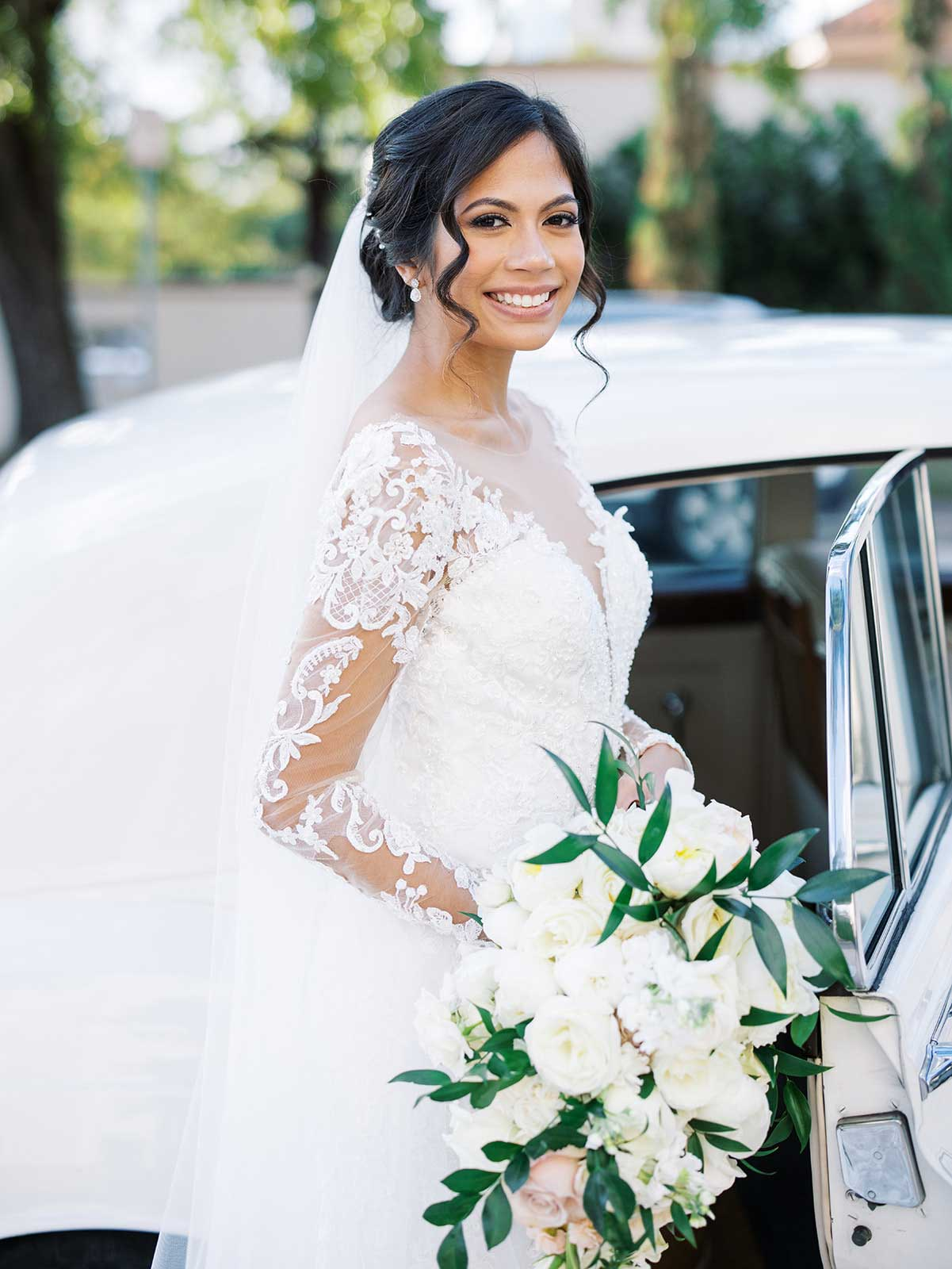 bride smiles near wedding car holding her bouquet with white roses.