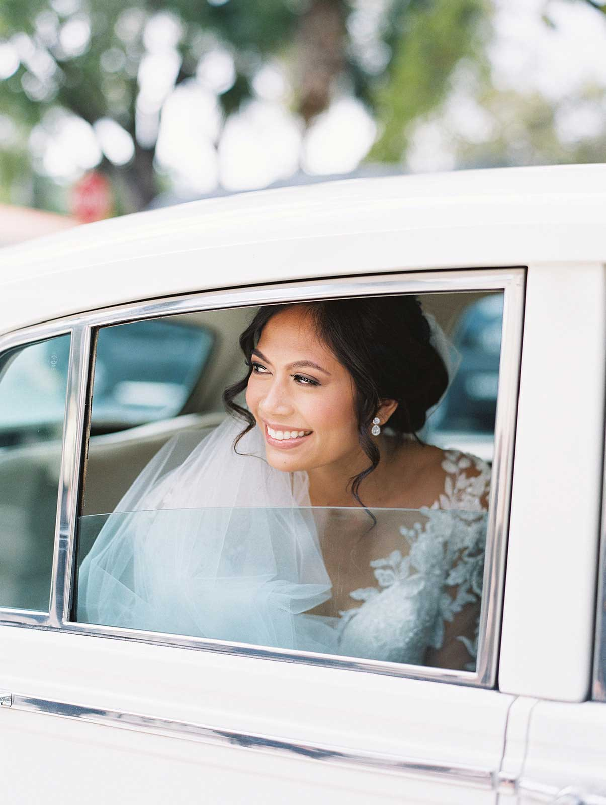 bride smiles from window of wedding car.
