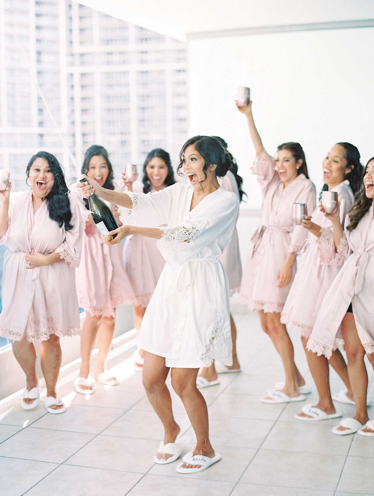 bride popping champagne with bridesmaids on balcony wearing their matching robes and slippers.