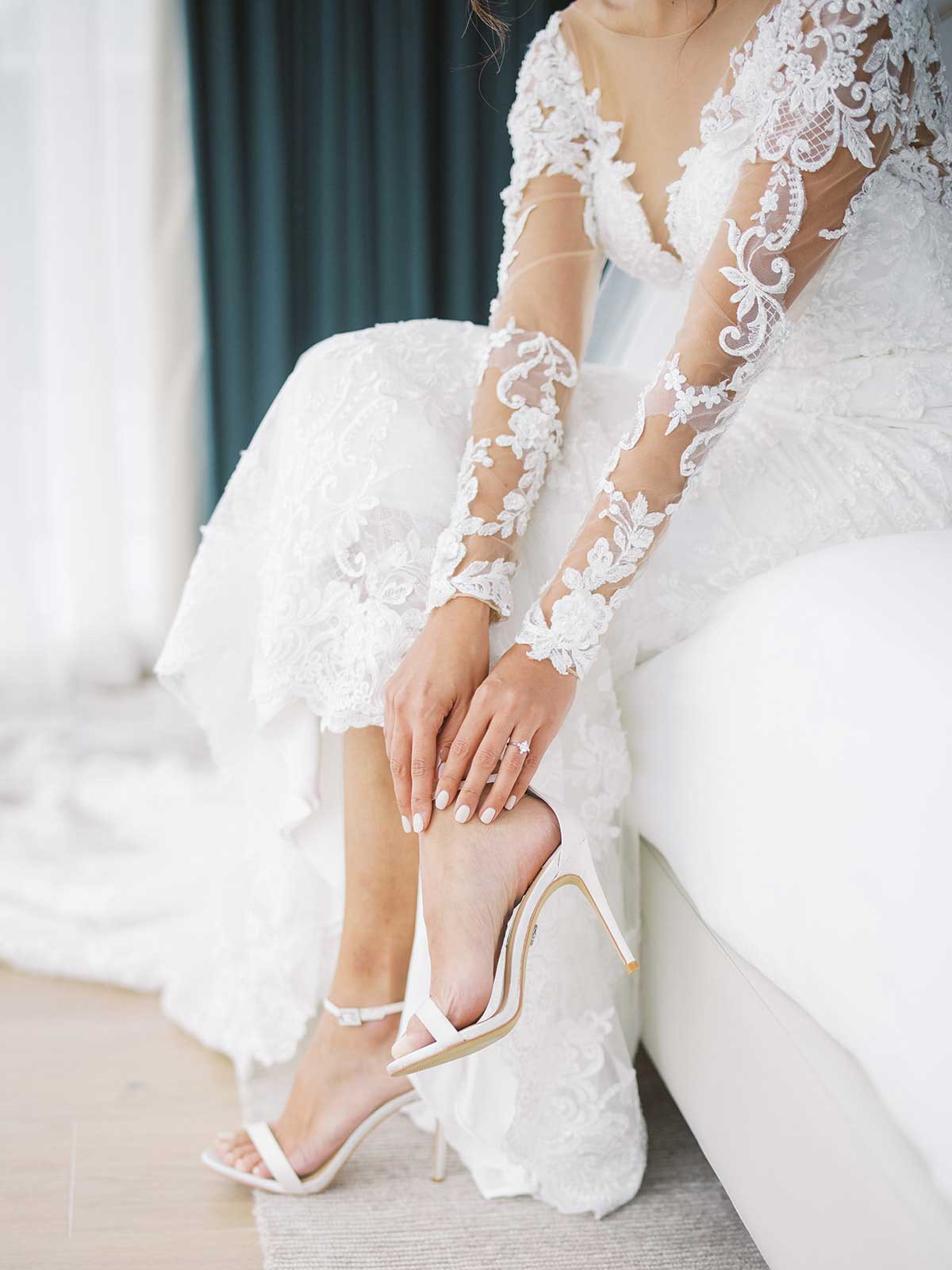 bride sits while putting on her shoes.