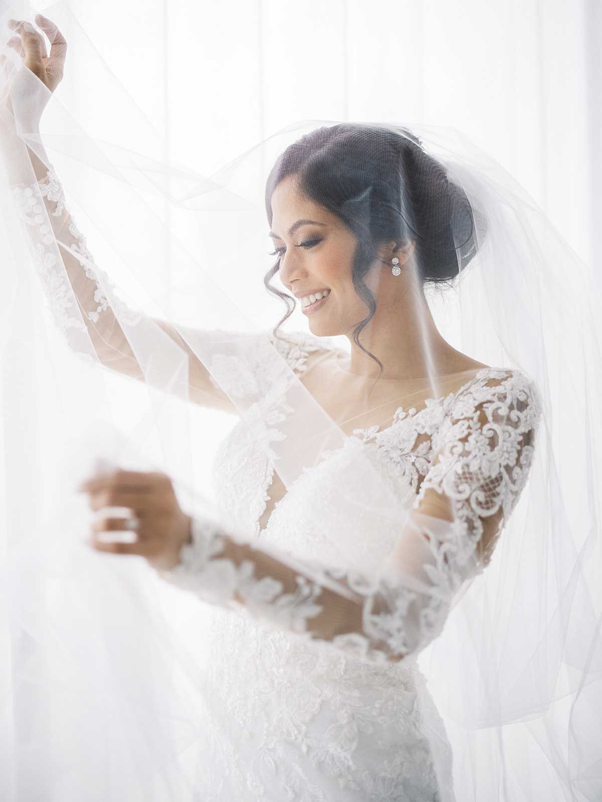 bride in her lace with sleeves gown with her veil draped around her.