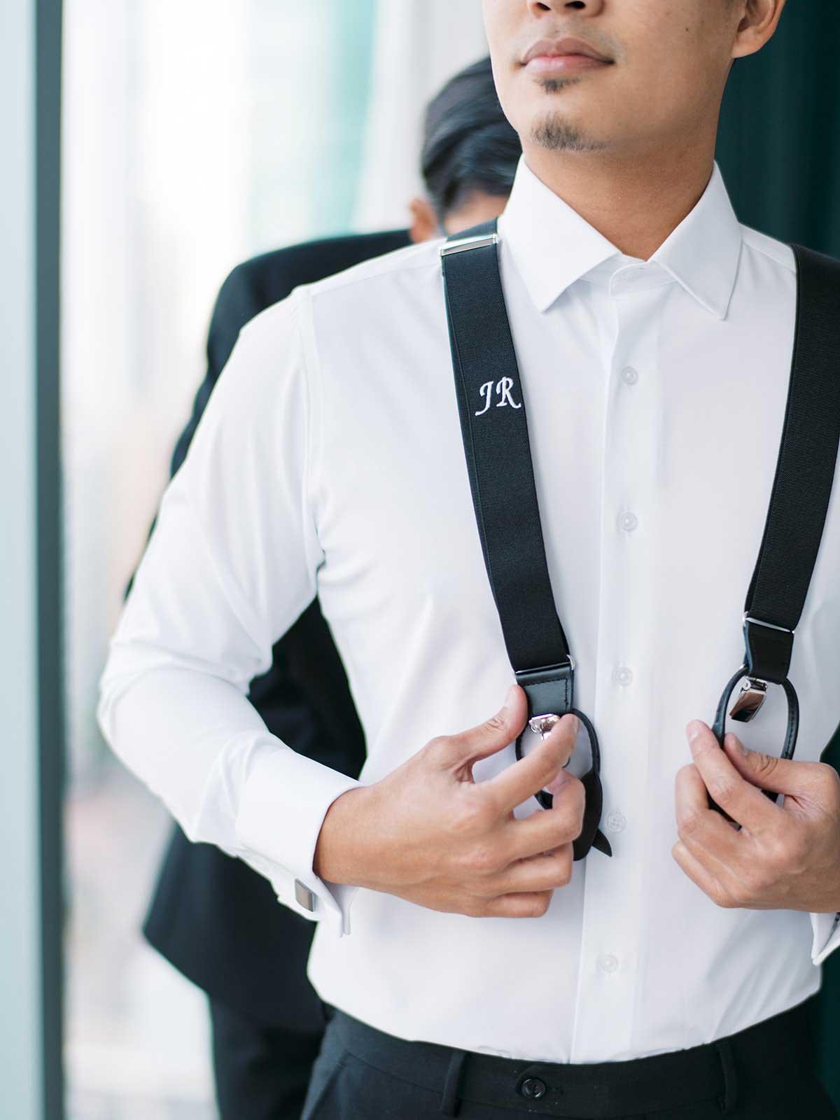 groomsman helping groom fasten his monogrammed suspenders.