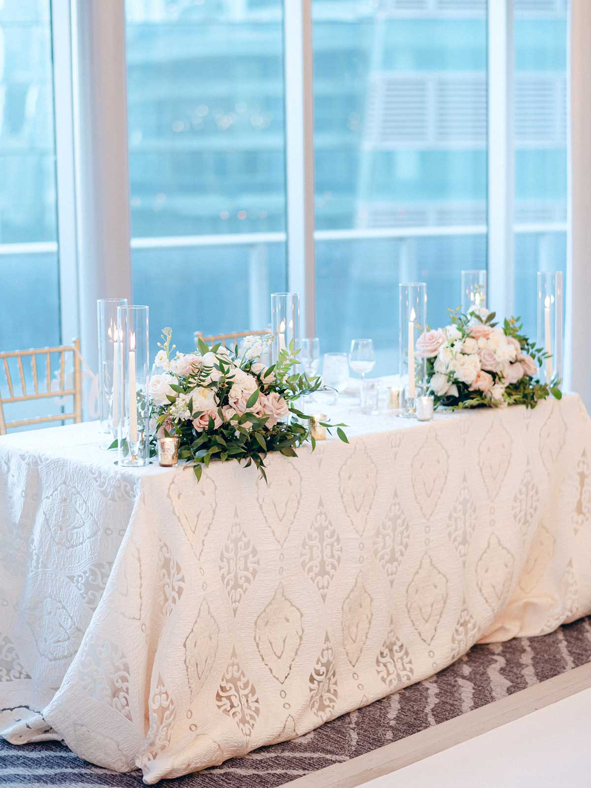 head table with white lace table cloth and floral centerpieces.