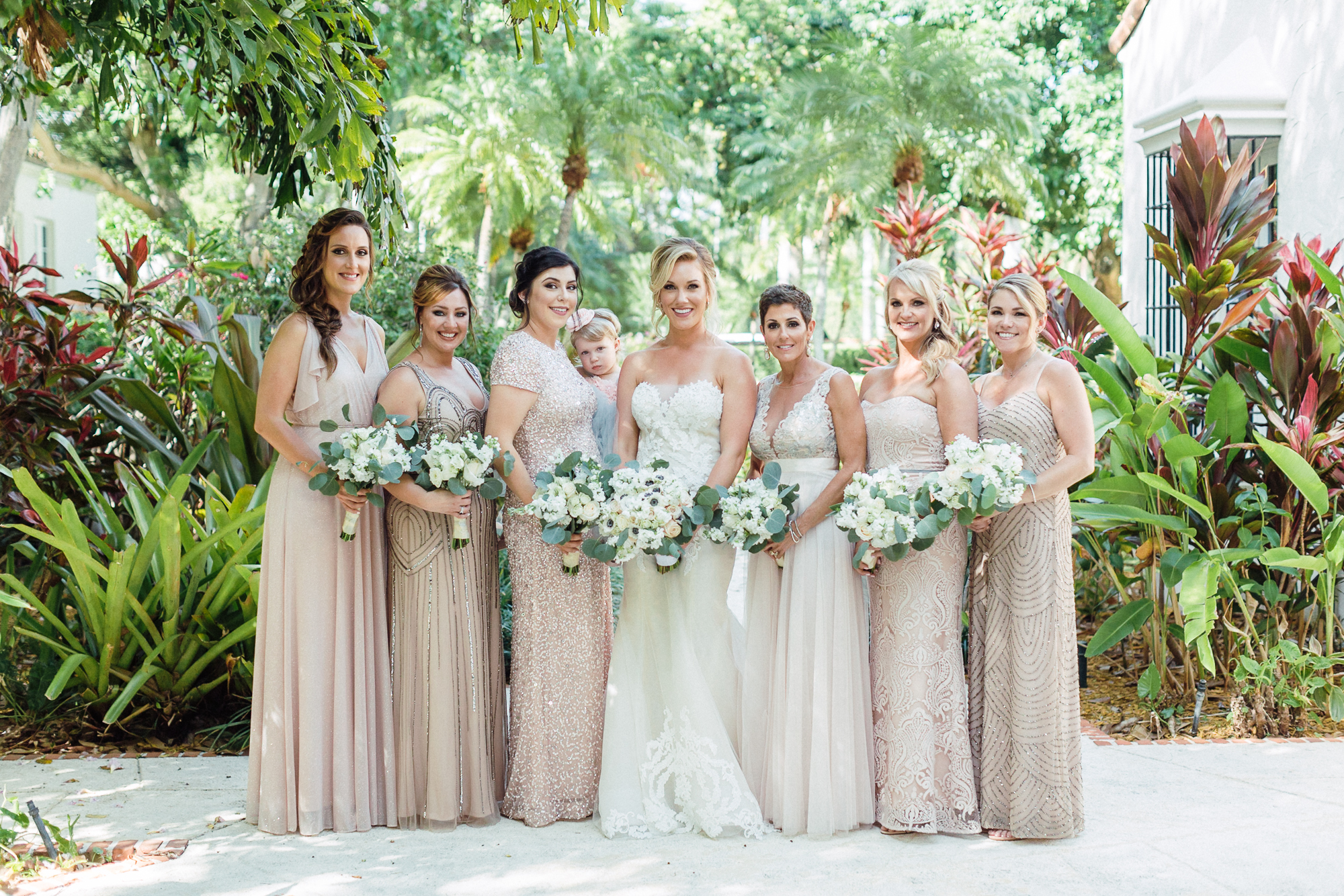 Bride stands with her bridal party wearing blush mix-matched gowns and holding their bouquets.