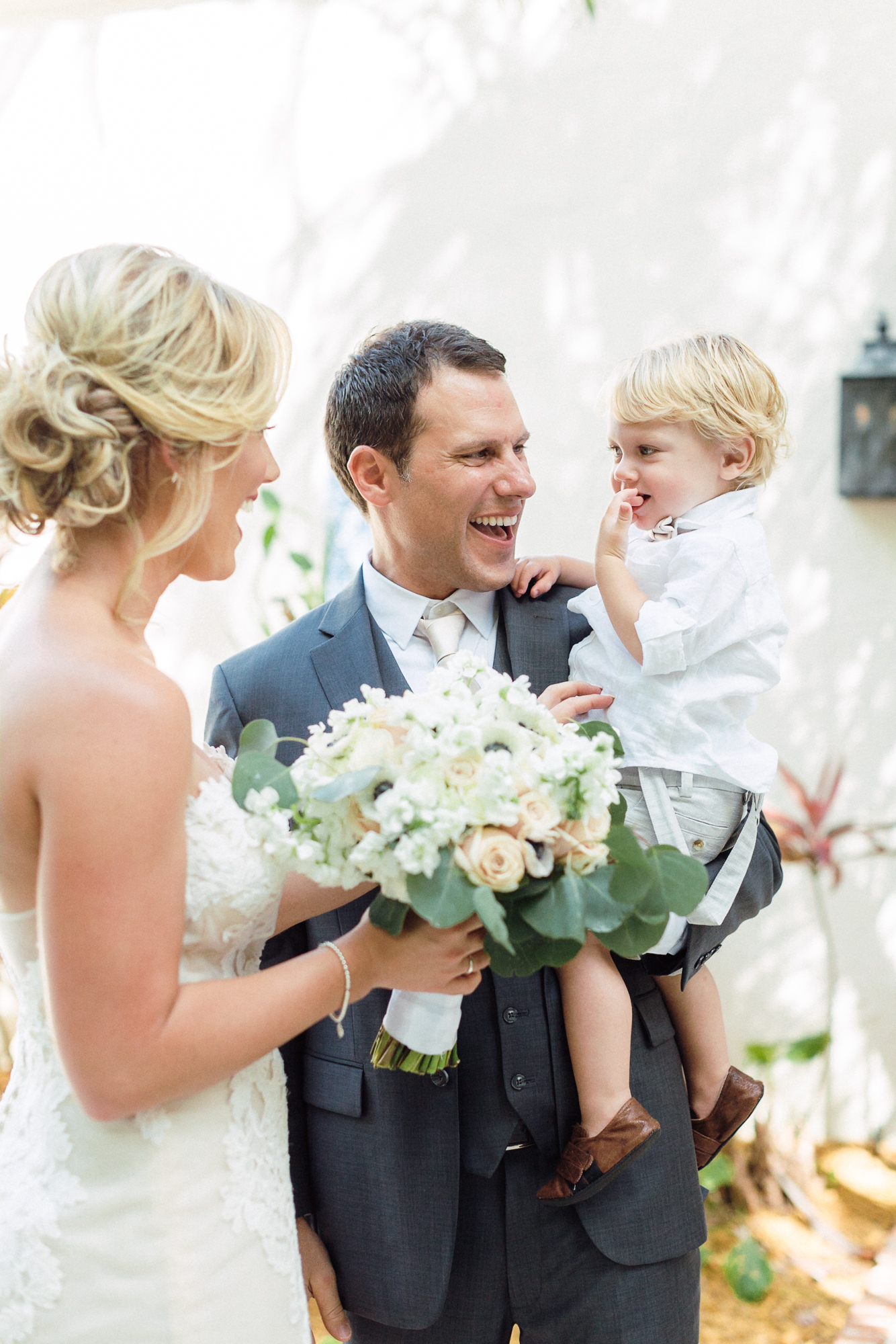 Groom carries couple's son while bride smiles at them holding her bouquet.