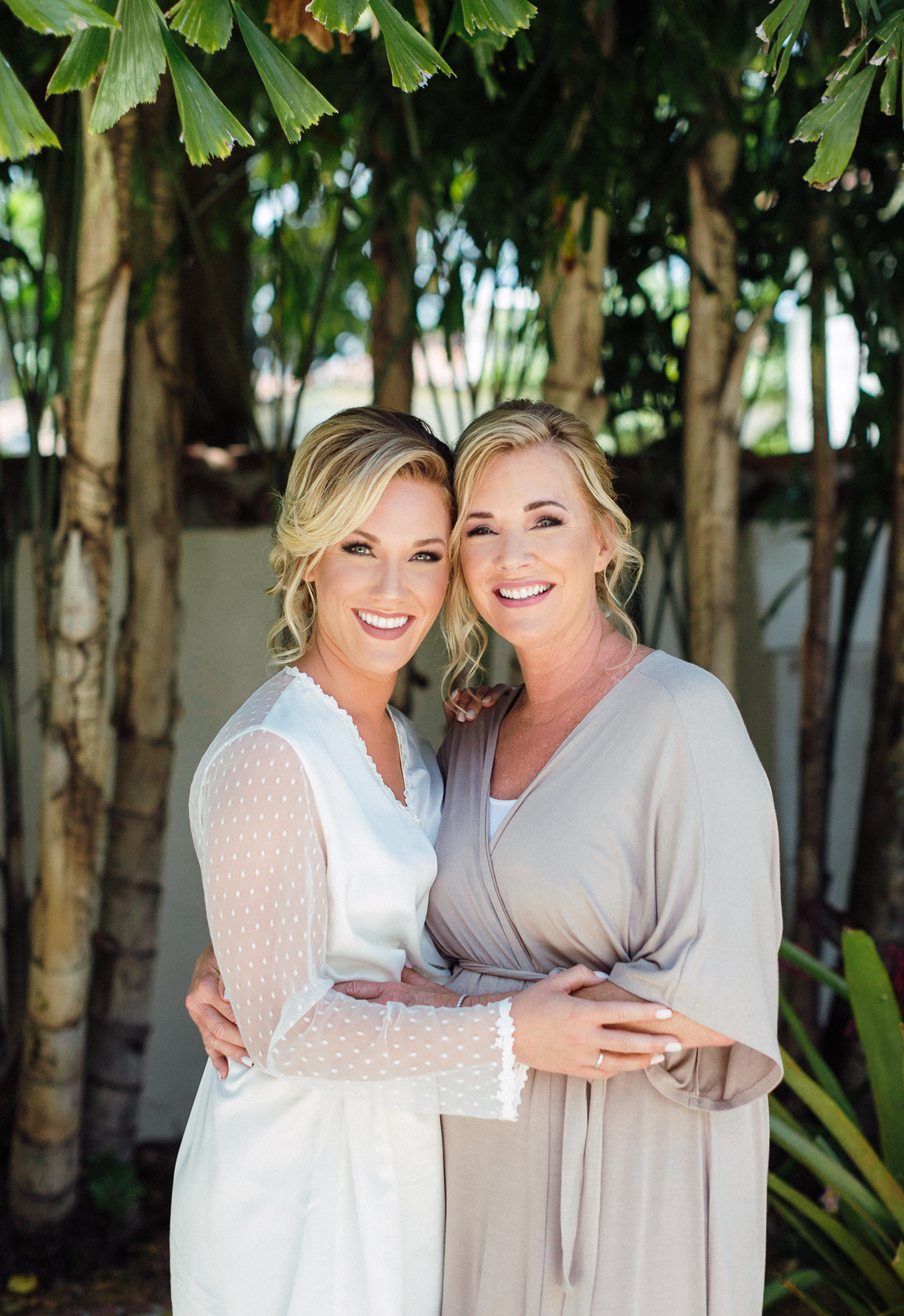 Bride and mother of the bride embrace each other outside in their getting ready robes.