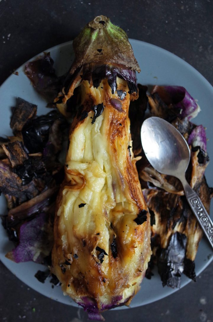 Flame Roasted Aubergine on a plate with the blackened skin peeling off
