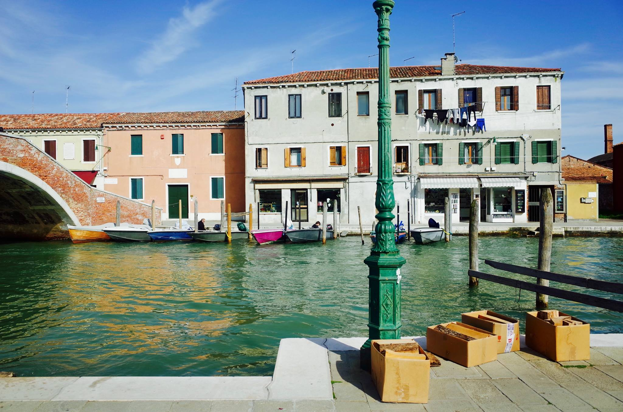 A canal in Venice, Italy, with buildings in the background, a bridge, and a green lamppost