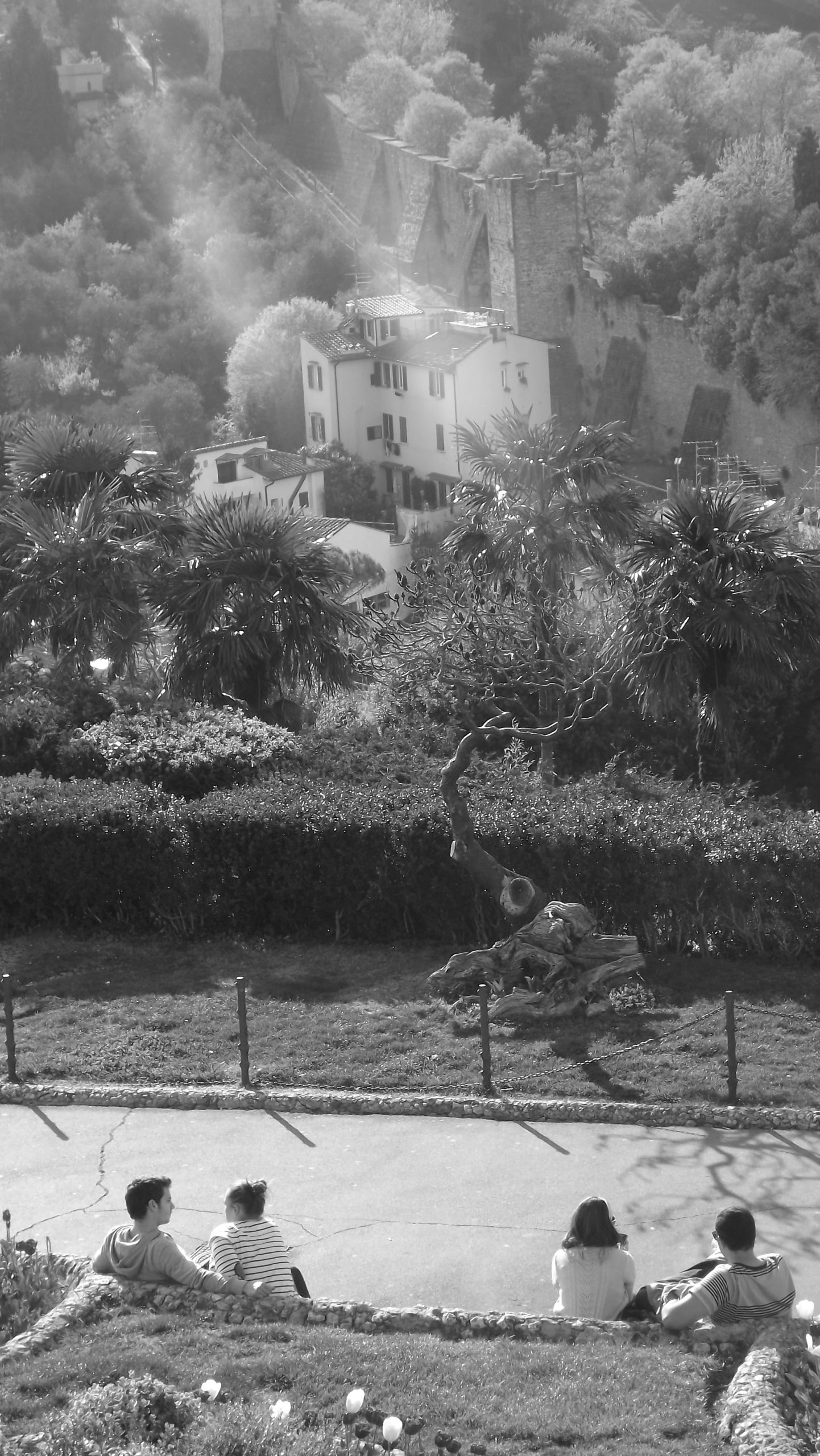 Black and White photo of couples sitting in-front of a Vista in Florence, Italy, with a view of a valley, trees, villa and wall