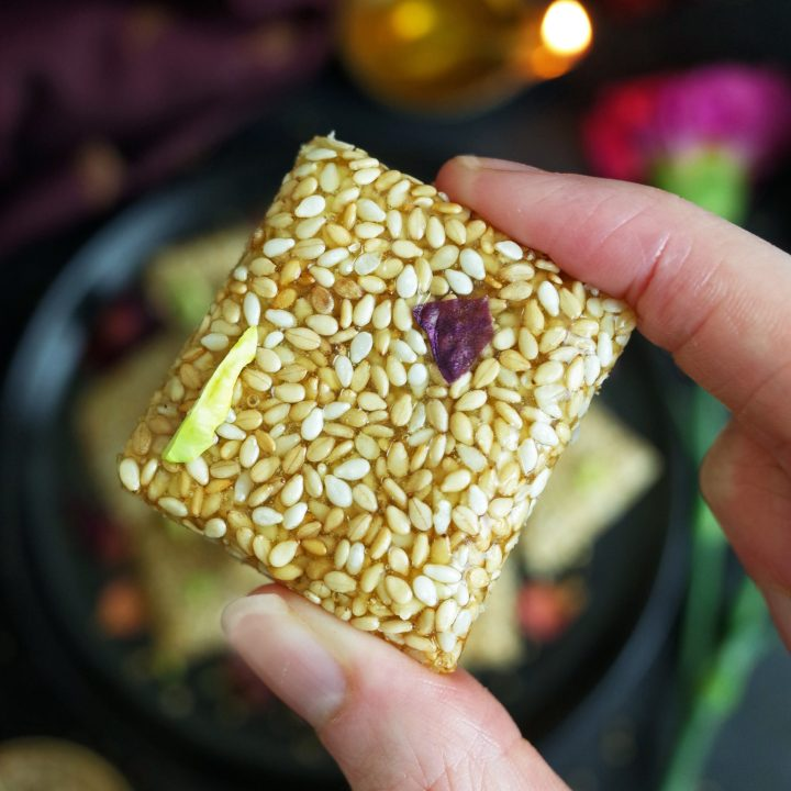 A hand holding up a piece of Maharashtrian Til Chikki topped with pistachios and rose petals