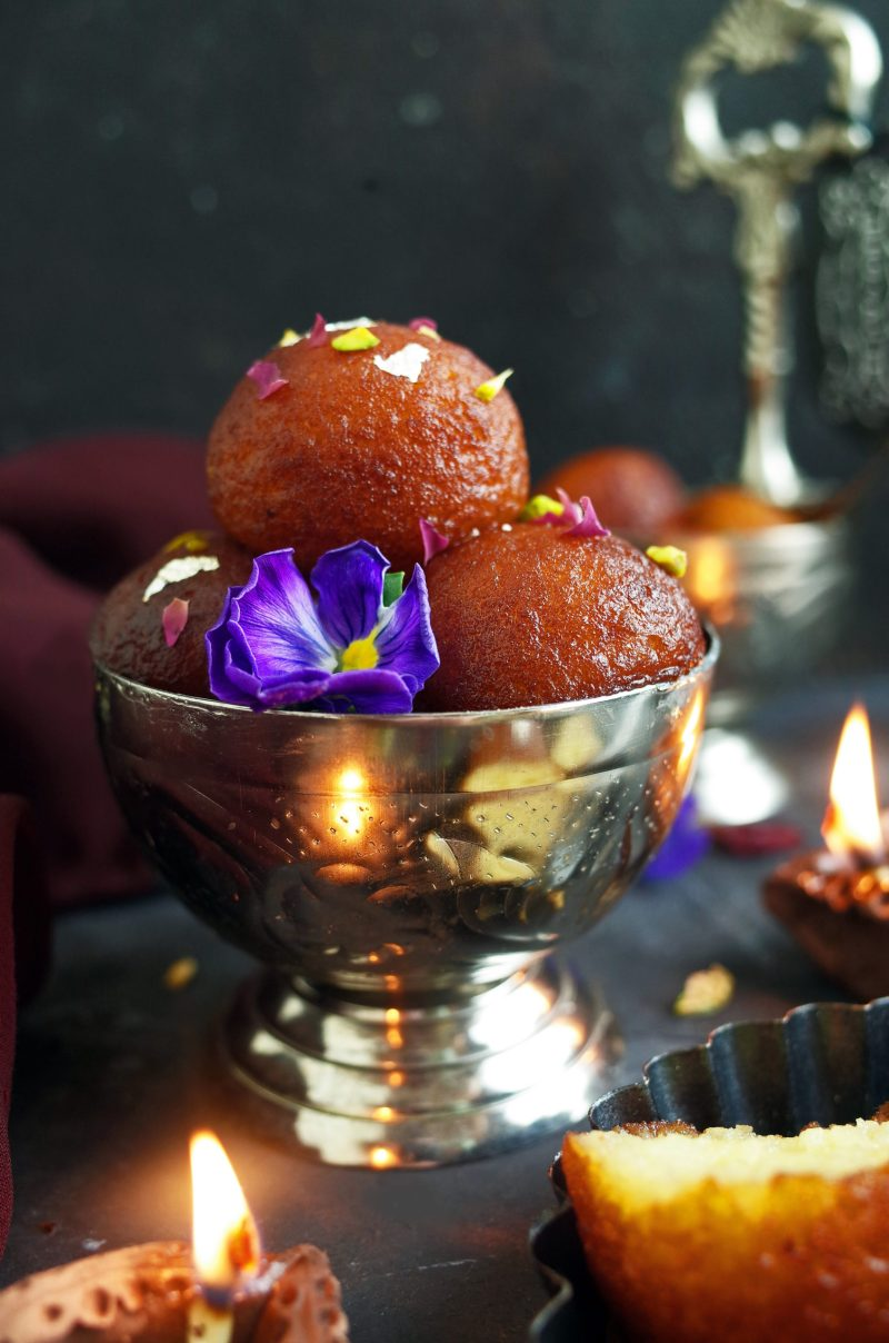 A pile of Indian Gulab Jamun topped with pistachios in a decorative metal bowl along with a pansy