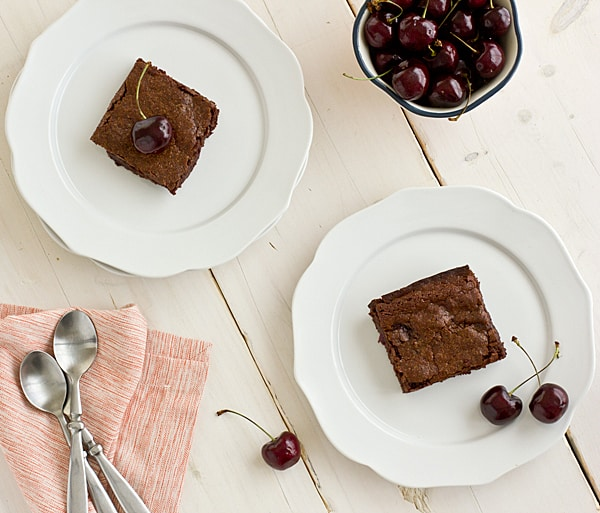 Brownies and fresh cherries rest on white china plates on a whitewashed tabletop