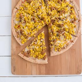 Sweet Corn, Sausage & Thyme Pizza sitting on wooden plate