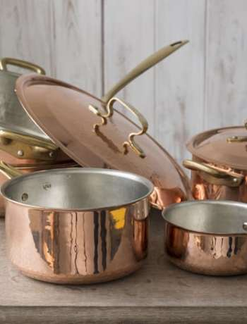 A set of copper cookware that include a small and medium-sized saucepan, a large saucepan, pot, and cover stacked on top of the other, and a covered small pot, all placed on a wooden countertop.
