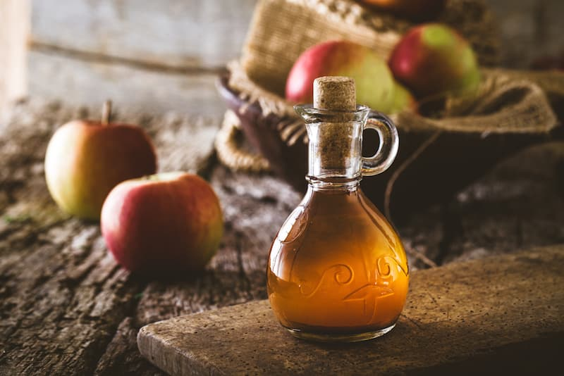 Apple vinegar. Bottle of apple organic vinegar on wooden background. Healthy organic food.