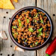 vegetarian chili with cilantro on a dark wood background. the toning. selective focus
