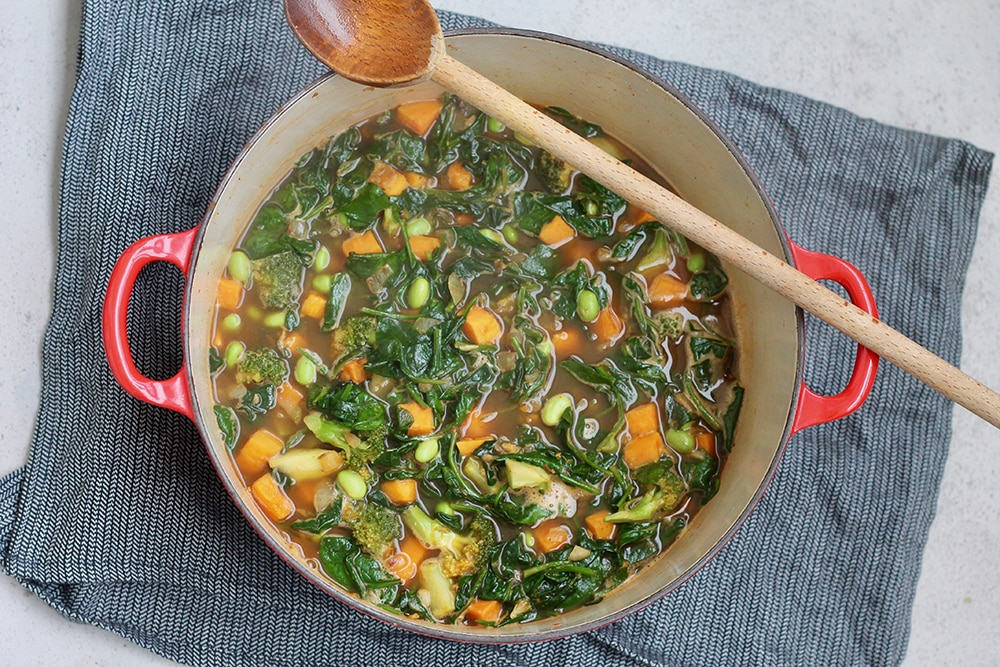 A large red soup pot is filled with the makings for winter green soup. Spinach, sweet potatoes, edamame, and broccoli make up the pot's contents and a wooden spoon rests on the lip of the pot.