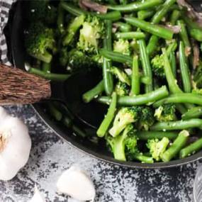 green beans and broccoli stir fry in a cast iron skillet next to a large garlic clove on a marble surface