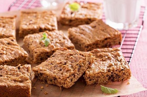Vegan almond butter blondies sit on a wooden block with sprigs of mint