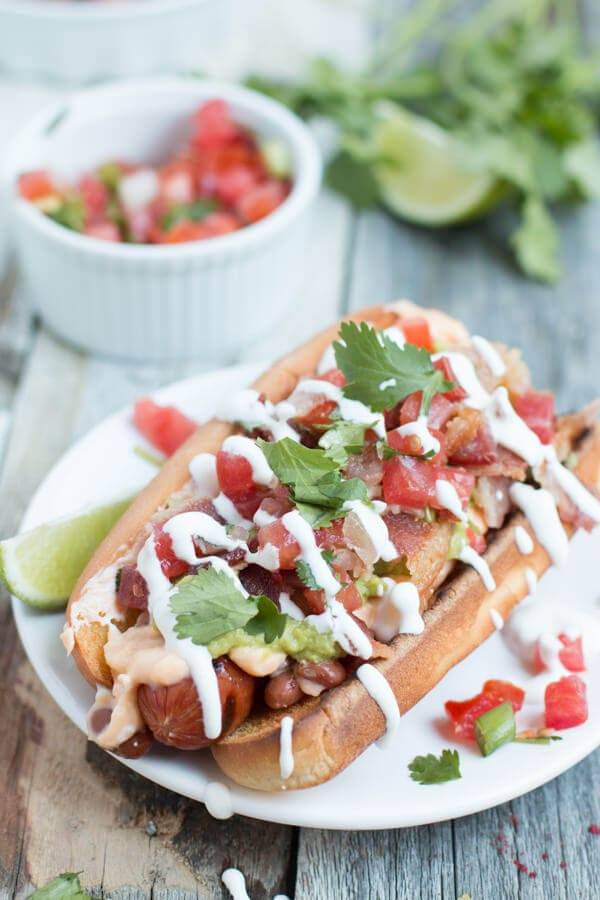 Sonoran hot dogs are like the ultimate hot dog. Loaded with beans, cheese sauce, bacon, pico de gallo, guacamole, and sour cream! ohsweetbasil.com-9
