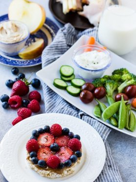 a grey board with different nutritious snack options for kids including rice cakes with almond butter and fruit, veggies and dip, apples and dip and a glass of milk