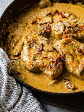 A black cast iron skillet with a creamy sauce full of sun dried tomatoes, mushrooms and seasoning over perfectly cooked chicken