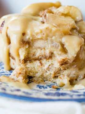 a large slice of apple pie bread pudding with vanilla sauce sitting on a blue china plate with a bite taken out of the front.