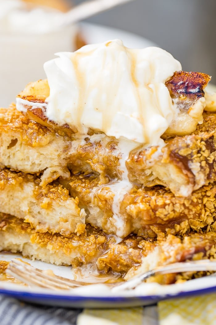 a stack of fluffy french toast with a cornflake crust, banana foster syrup and a dollop of whipped cream